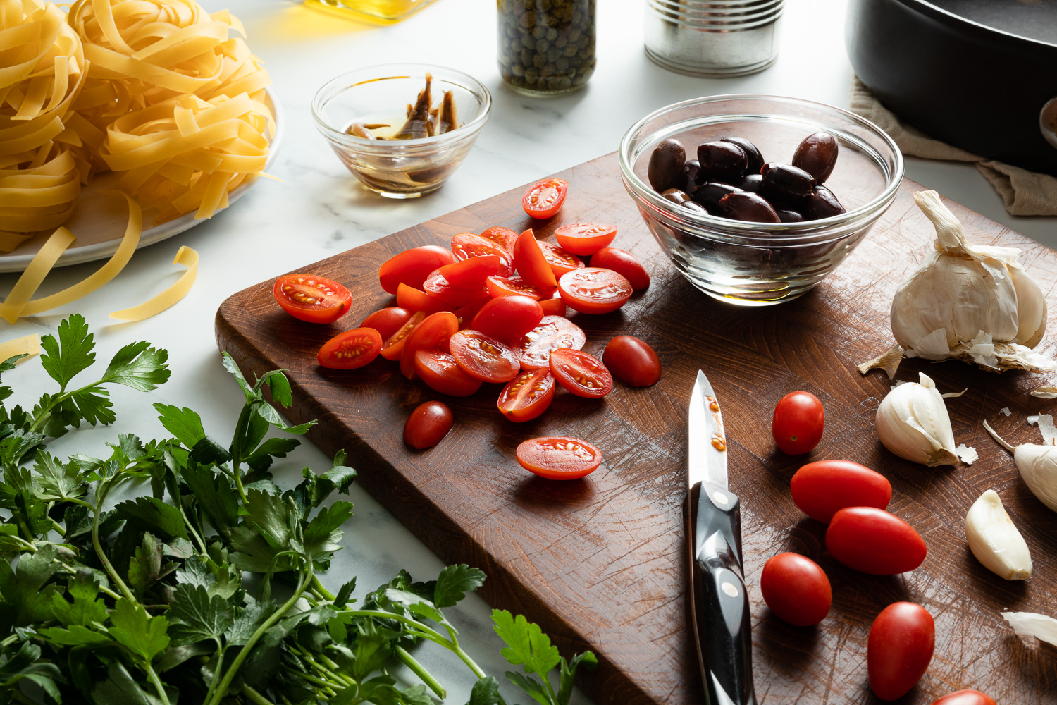 tomatoes, olives, garlic, and a paring knife on a cutting board with parsley and pasta